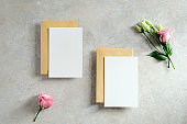 Blank paper cards with envelopes and flowers on concrete table. Wedding invitation card mockup. Flat lay, top view.