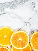 Colorful orange citrus slice fruit texture background on white marble table