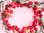 Cherry berry frame with flowers and petals in water on pink background