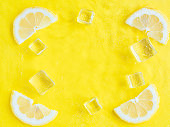 Intense yellow lemon citrus slice in cool water with ripples texture summer background with ice cube