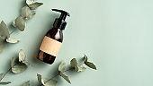 Amber glass dispenser bottle mockup and eucalyptus leaves on green background. SPA natural organic beauty product packaging design, branding.