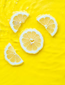 Intense yellow lemon citrus slice in water with ripples texture summer background