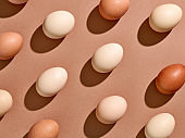 Egg pattern with hard shadow on brown background, from above