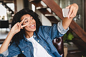 Happy afro young woman taking selfie on her phone in the living room. African businesswoman in home office. Beautiful young women making selfie photo in the home office.