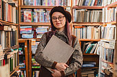 Portrait of an attractive cheerful 20s female hipster in glasses holding a book at bookstore or library
