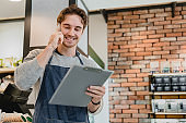 Busy attractive young barista talking on phone holding folder in coffee shop with brick wall in the background
