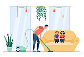 Father vacuuming living room while children sitting on sofa