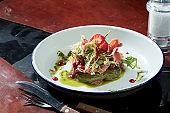Salad with strawberries, prosciutto, pesto sauce in a white plate. Dark background. Hard light