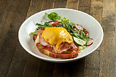 Delicious and great breakfast - croissant sandwich with ham, melted cheese, tomatoes with mixed salad, served in a white bowl on a wooden background
