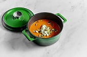 Appetizing and healthy pumpkin cream soup in a green bowl on a marble background. Orange cream soup with cheese mousse