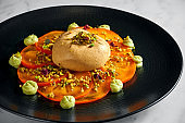 Buratta cheese with persimmon and pistachio in a black plate on a light marble background