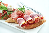 Set of delicious Italian bruschettas with ham, ham, tomatoes, salmon and cheese served with a glass of wine