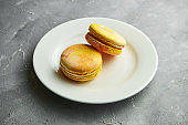 Appetizing almond flour Macaroon cookies with mango interlayer served in a white plate on a gray background