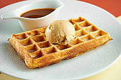 Classic Belgian waffles with ice cream and sweet sauce in a white plate on colored backgrounds.