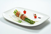 Grilled asparagus with bacon and mustard sauce in a white plate. Isolated on gery background.