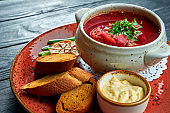 Traditional Ukrainian borscht with rib and sour cream, served in a red plate with rye bread and aromatic butter on a dark background. Red soup