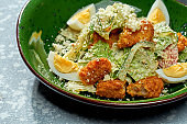 Appetizing salad with chicken breaded and deep fried, parmesan, egg, lettuce and white sauce in a green plate on a blue background
