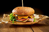Juicy burger with beef, salad, pickles, bacon and cheddar cheese, served on parchment on a wooden background. American fast food