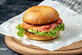 Delicious burger with chicken, tomatoes, lettuce, cucumber melted cheese on white parchment. Dark background. American fast food. Chickenburger