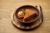 Appetizing carrot cake with apple sorbet ice cream in a clay bowl on a wooden background. A healthy dessert. Pastry