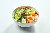 Delicious veggie bowl with salmon, avocado, cucumber, cherry tomatoes and mix salad in a white plate. Isolated on grey background.