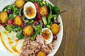 Classic nicoise salad with boiled egg, potatoes, tuna, olives and white sauce, served in a white bowl on a wooden plate. A delicious and healthy seafood salad