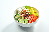 Delicious veggie bowl with cucumber, bell pepper, salad mix, quinoa and tofu in a white plate. Isolated on grey background.