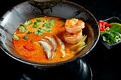 Asian tom yum soup with shrimps, shiitake mushrooms, octopus, tomatoes and rice in a plate. Classic Asian cuisine. Food delivery. Isolated on black