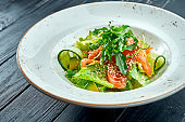 Appetizing, dietary salad with lettuce, cucumber, avocado and lightly salted salmon in a white plate on a dark wood background. Healthy food