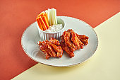 Wings in barbecue sauce with white sauce and carrots, cucumber in a white plate on colored backgrounds. Fingerood and Pub