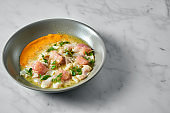 Peruvian cuisine dish - seabass ceviche with grapefruit and yellow sauce, served in a grey plate on a marble background. Restaurant seafood.
