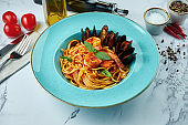 Appetizing Italian pasta with tiger prawns, tomato sauce, Chilean mussels in a blue plate on a marble background. Spaghetti with seafood