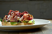 Huge sandwich with jamon crudo, brie cheese, mixed salad, grapes, sun-dried tomatoes and nuts on rye bread, served in a white plate on a wooden background. Delicious breakfast toast