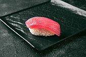 Nigiri sushi with tuna on a black board. Japanese kitchen. Food delivery. Black background