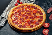 Appetizing pizza with red sauce, tomatoes, salami and cheese. Dark background. Italian Cuisine