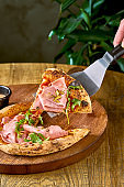 Pizza with mortadela, arugula and pistachios on a wooden board. Italian Cuisine. Hand holds a piece of pizza on a spatula