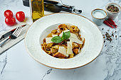 Appetizing Italian pasta with salmon, sun-dried tomatoes and parmesan in a white plate on a marble background. Fettuccine with seafood