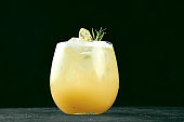 Alcoholic cocktail with gin and orange juice, lime and mint in a glass with ice
