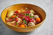 Chicken soup with noodles, yolks, and meatballs on a marble background