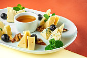 Appetizer - antipasti cheese plate with dorblu, parmesan and camembert, honey, nuts on bright colored backgrounds