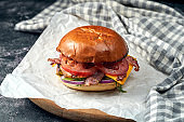 Delicious burger with beef, tomatoes, lettuce, melted cheese and bacon on white parchment. Dark background. American fast food