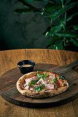 Pizza with mortadela, arugula and pistachios on a wooden board. Italian Cuisine