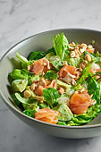 Fresh salad with salmon, delicate cheese, peanuts and mint in a gray bowl on a white marble background