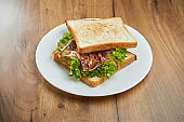 Delicious snack - toast sandwich with sun-dried tomatoes and jamon, sauce in a white plate on a wooden background