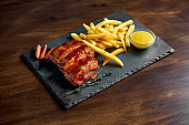 Appetizing beer snack - BBQ pork ribs in honey sauce and French fries, served on a black plate. Wood background.