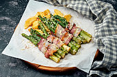 Grilled asparagus with bacon, parmesan cheese and potatoes on white parchment. Dark background