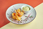 Appetizer - tempura fried shrimps with sauce in a white plate on colored backgrounds. Fingerfood, pub