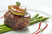 Portion of grilled mignon steak with foie gras and asparagus, berry sauce in a white plate. Isolated on grey background.