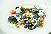 Delicious cuttlefish ink ravioli stuffed with shrimps and scallops, served with white sauce, cherry tomatoes and olives in a white plate on a white tablecloth. Black ravioli pasta