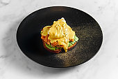 Appetizing and healthy breakfast - toast with avocado, baked tomatoes, poached egg and hollandaise sauce, served in a black plate on a marble background